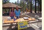 Color photo of two young ladies posing in front of the Sun Print booth during the Earth Day event.
