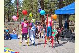 Color photo of performers from Willy Woggle's Circus on stilts during the Earth Day event.