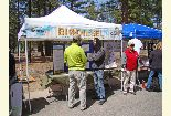 Color photo of people chatting in front of the Bio Diesel booth during the Earth Day event.