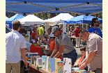 Color photo of members of the public checking out the library booth during the Earth Day event.