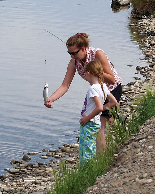 Mom helps child reel in a fish