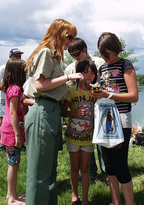Forest service employee helps kids learn how to use the GPS unit