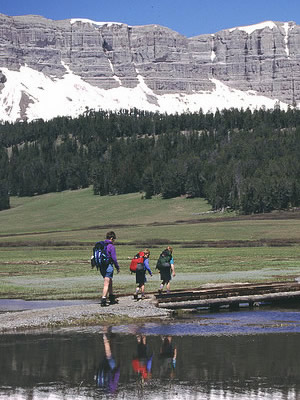 Day hikers along the shore of Brooks Lake with Breccia Cliffs in background in the Shoshone National Forest, located in northwestern Wyoming
