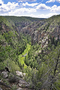 Photo: looking into a canyon with green grass and patches of water at the bottom