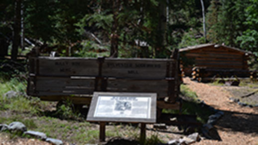 Entrance to Miner's Park with a sign and a wagon in the foreground and a cabin in the background