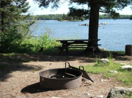 A campsite with a fire grate and picnic table on the lake's edge at Lake Jeannette Campground.
