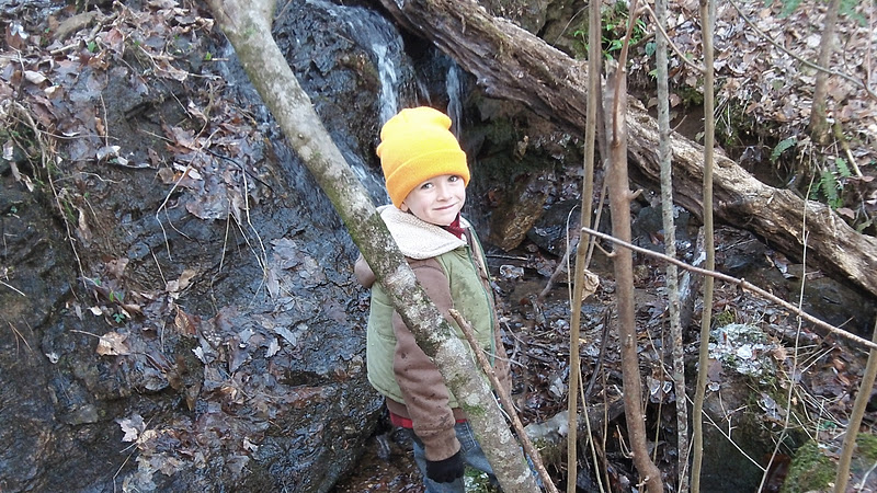 A child sports a blaze orange hat for safe hiking in the fall