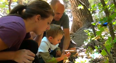 Photo taken from a video of the couple and a small boy bending over viewing fall color leaves.