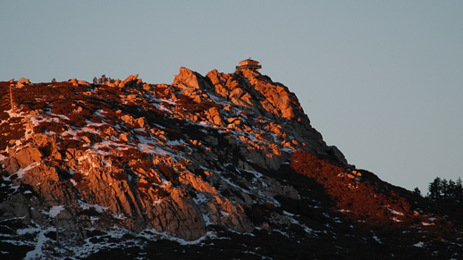 The sun is setting in the West, casting beautiful warm colors over the Bulter Peak Fire Lookout Interpretive site.