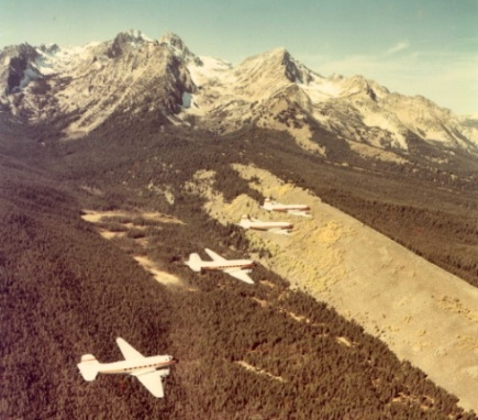 This historical photo was taken of four DC-3 planes flying over a mountain range.