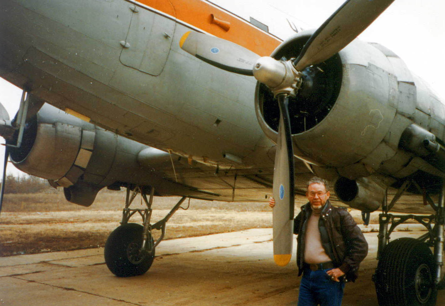 This photo shows the DC-3 before turbine conversion and new paint and a man standing next to it.