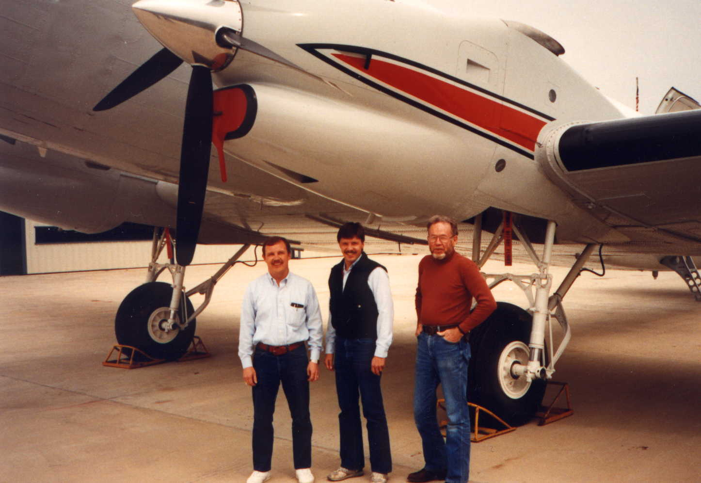 Photo of the DC-3 after it received a turbine conversion and new paint, three men standing near it.