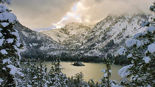 View of Emerald Bay surrounded by snow on trees and moutains, near the Lake Tahoe Basin.