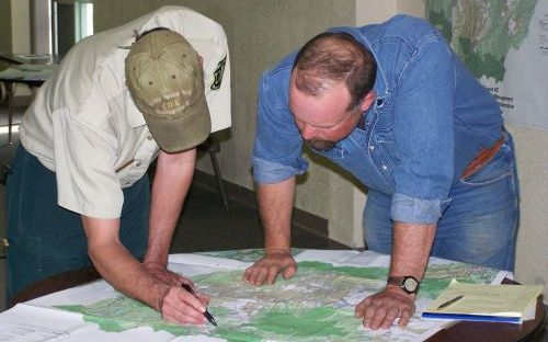 Image of two men looking over a topographic map