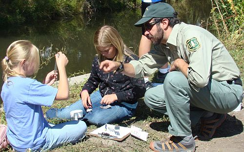 Image of Forest service hydrologist showing test tube to group of children