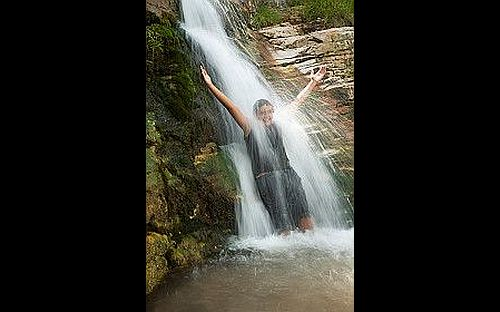 Image of a young boy with arms stretched out smiling under a waterfall
