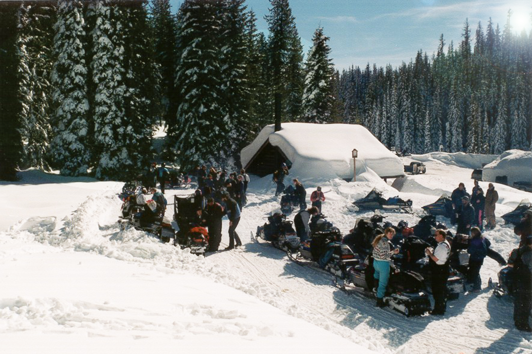 A large group of snowmobilers gathered at Lolo Pass on a wintry afternoon.