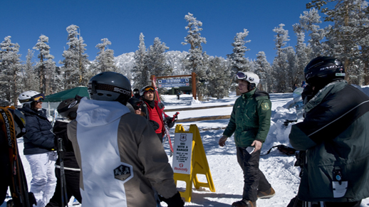 Color photo of Ranger Caleb talking to a group of skiers.