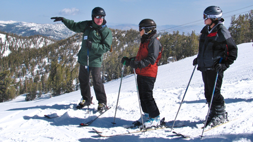 Color photo of Ranger Jeff standing on a ski run talking to two skiers.