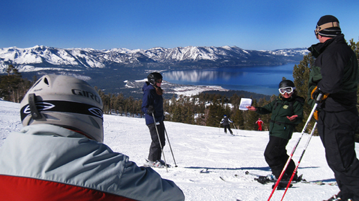 Color photo of Ranger Tara standing on a ski run talking to a group of skiers and snowboarders.