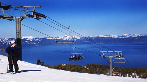 Color photo of a ski lift with Lake Tahoe in the background