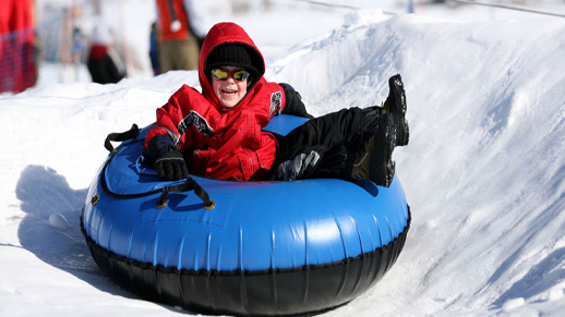 A child on a blue snow tube slides down the hill.