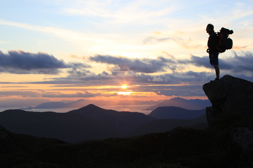 Hiker standing on a rock viewing a cloudy sunset behind the mountains.