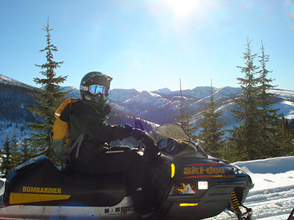 A happy snowmobilier poses in the sun and snow on the trail at Lolo Pass Visitor Center