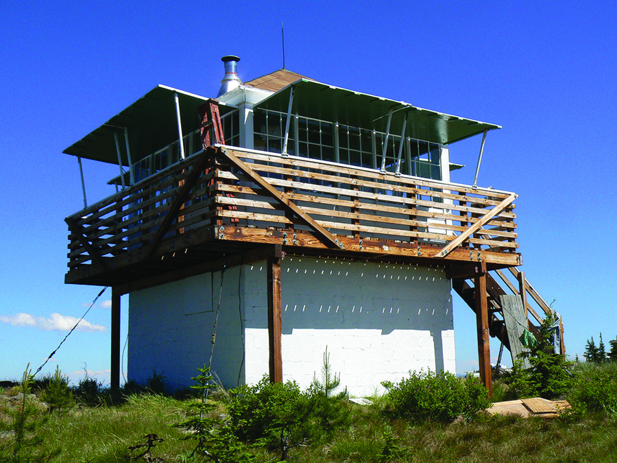 The historic Scurvy Lookout towers into the sky with whispy white clouds in the background.