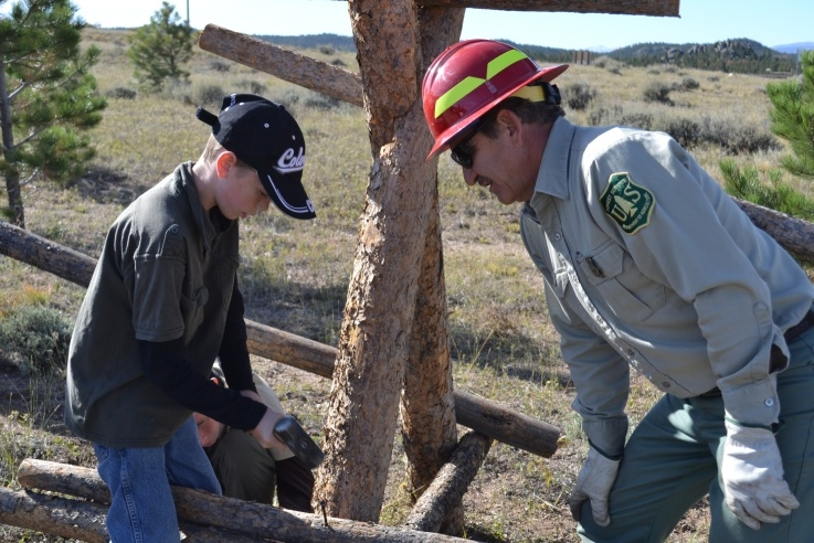 A Forest Service Employee helps a youth Volunteer fix a fence at National Public Lands Day