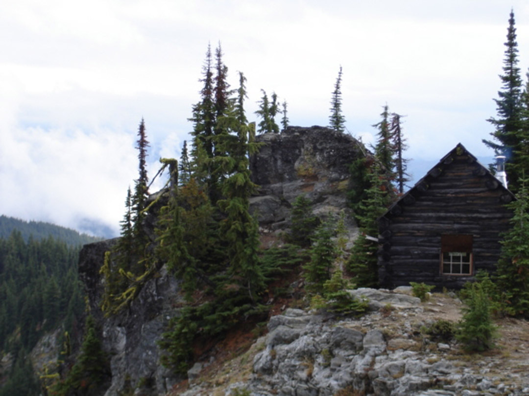 The Colds Springs Peak Cabin sits among steep cliffs and evergreen trees.