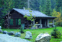 The historic Kelly Forks Cabin sits peacefully in a lush forested setting.