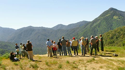 A group of people view a mountain landscape.