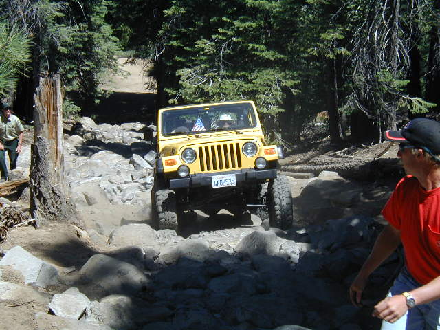 Color photo of a jeep climbing a steep rock hill