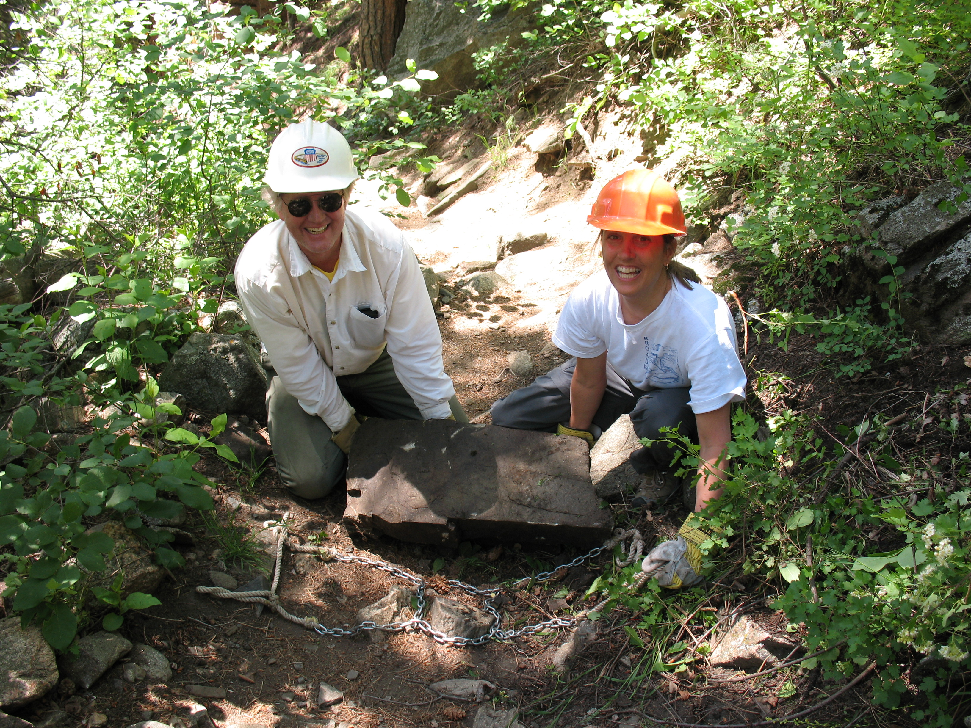Two people placing a rock on a dirt trail next to steep green ve, smiling and looking at the camera.