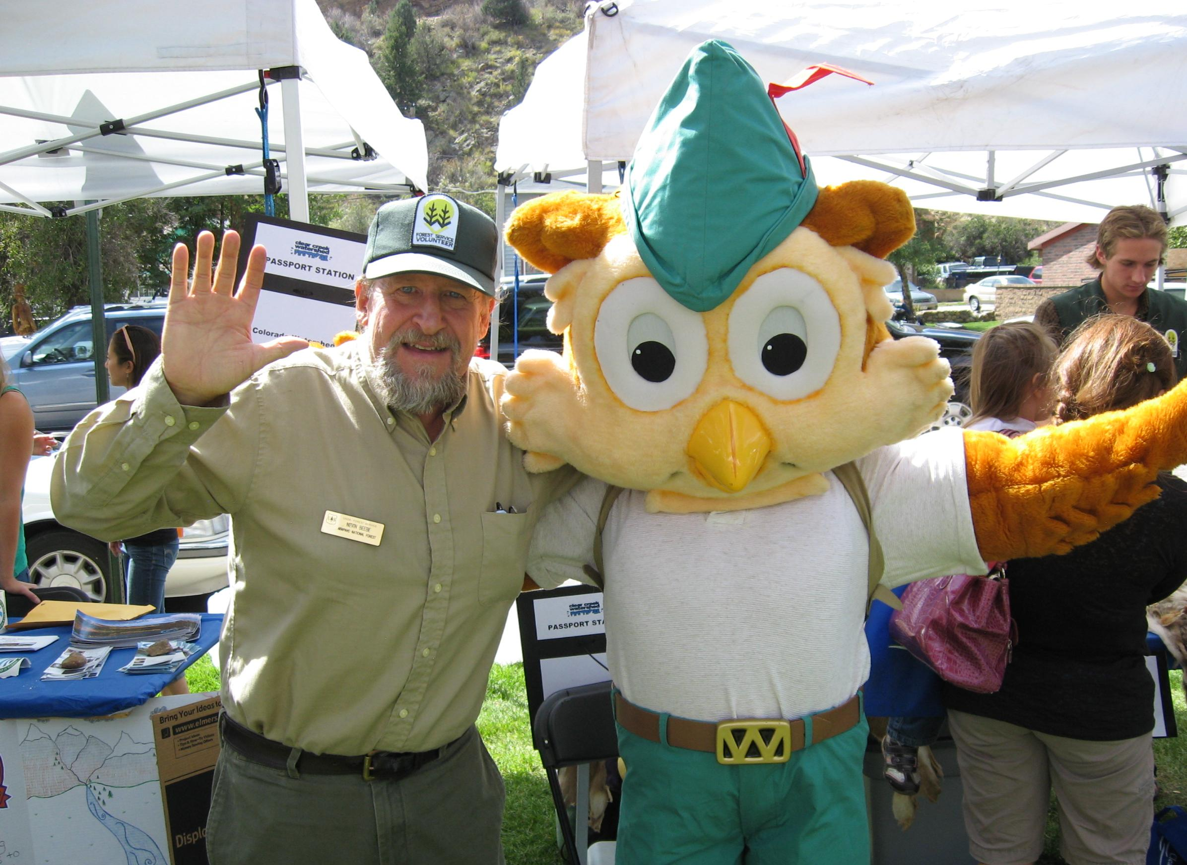 Woodsy Owl and Forest Service volunteer waving