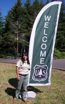 field ranger standing by tall Welcome Flag