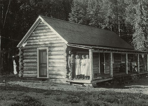 photo of the guard station in 1920 with four people standing on porch