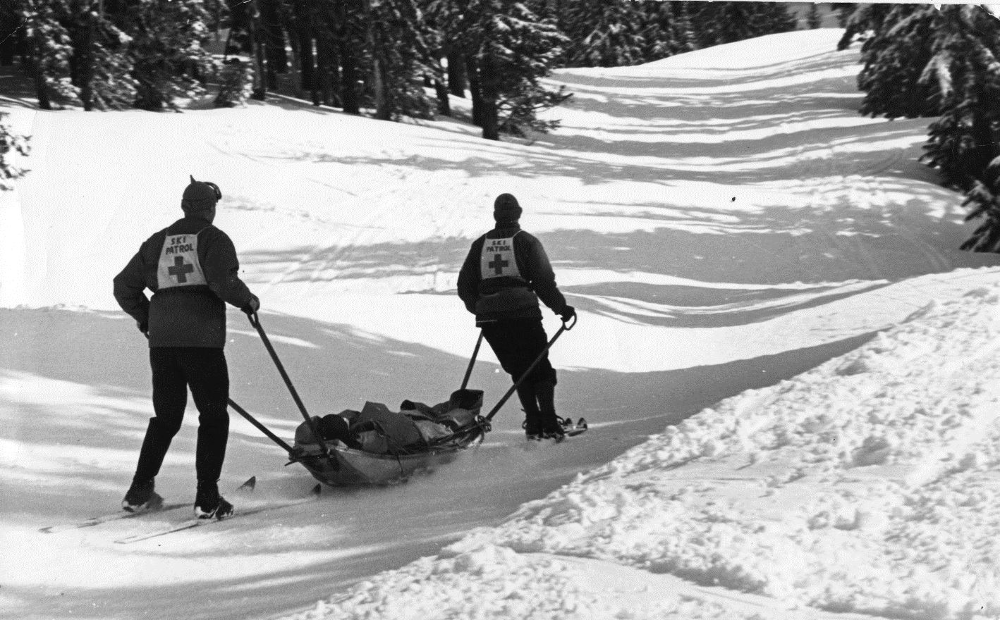 Two ski patrol members carrying a member of the public down for their safety