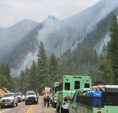 Green Fire vehicles line the road agains a smoky hillside.