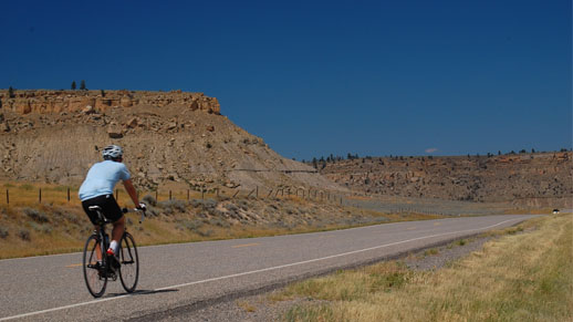 A cyclist rides past the bluffs near Canyon Creek Battlefield.