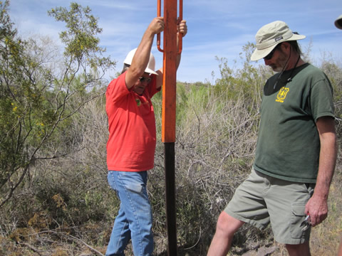 Two men pounding a post with a post pounder