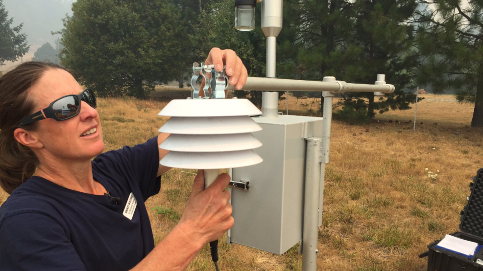 An air resource advisor adjusts an air quality monitoring station during the 2019 Milepost 97 fire near Canyonville, Oregon.