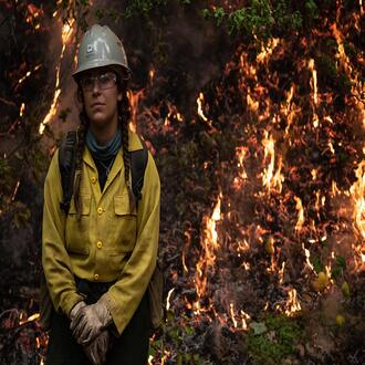 A female firefighter stands facing the camera in front of a back burn area.