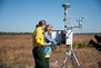 Photo of Forest Service scientists check an instrument that measures smoke concentrations downwind from a research burn. Randy Gon, U.S. Air Force