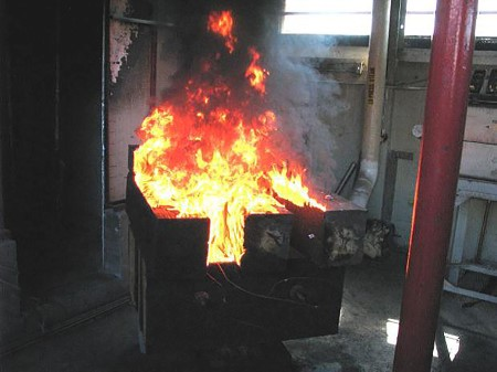Flames in wood crib of creosote-treated timbers, approximately eight minutes after application of hot metal wafer. Robert White, USDA Forest Service