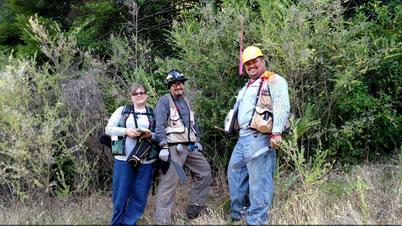 Photo of Field sampling on the Yurok Reservation, encroached by trees and shrubs. Shaonna Chase (left) Yurok Tribe GIS specialist, Frank K. Lake (center) Forest Service research ecologist, and Eldon Kinney (right) Humboldt State University student researcher. Joe Hostler, Yurok Tribe Environmental Program.