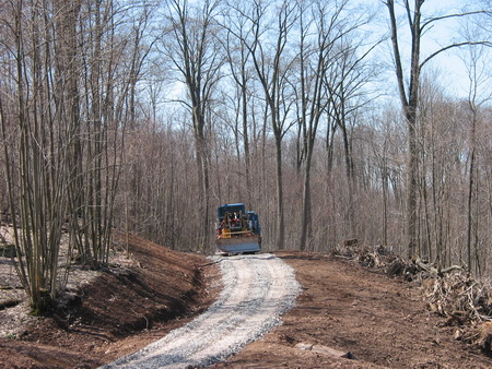 Photo of Gravel application to a newly constructed forest road to protect the road surface from erosion, and woody material from the road right-of-way positions as a windrow on the fillslope (right side of photo) to trap any sediment transported off the road.