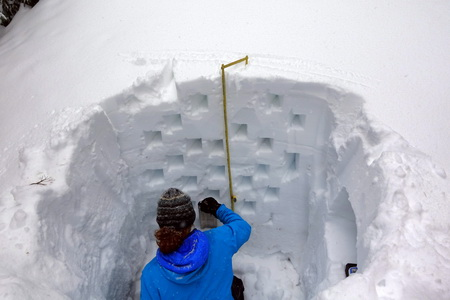 Photo of Researcher conducts research in a snow pit, measuring the depth of the snow and evaluating snow crystals to understand their stability and amount of water held in them.