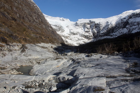 Photo of View upstream toward the wall failure that triggered the Cowee Creek tsunami, Alaska. Foreground shows the channel scoured to bedrock from the wave that originated in the lake below the cirque wall. The elevation of the scour line is 10 feet above the channel bottom.